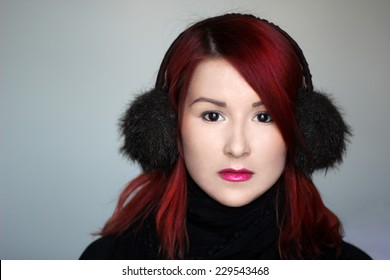 Redhead girl in the fur ear muffs and black scarf