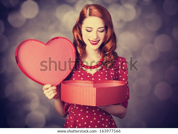 Redhead girl with gift for Valentines Day. Photo with bokeh at background