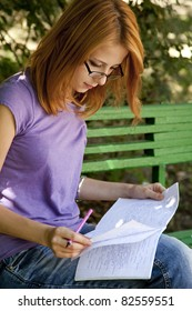 Redhead girl in glasses doing homework at the park.