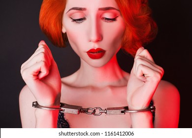 Redhead girl with handcuffs on black background. Sexual bdsm toy. Woman submission. Outfit for playing bdsm games. Lady with metal handcuffs on hands. Photo in low key lighting. Submission in society