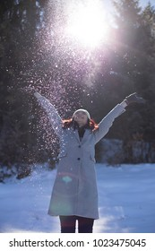 Redhead girl with her arms raised high with snow falling on her from above in foreground. Sun shining through trees in background.