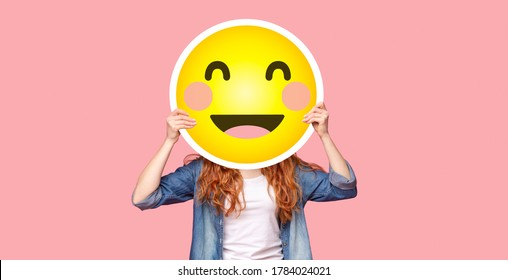 Redhead girl hiding her face behind happy emoji smile, posing over pink studio background, panorama with copy space
