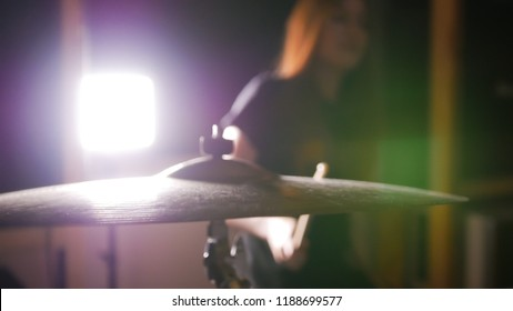 Redhead girl hitting a cymbal in a dark room. Close up