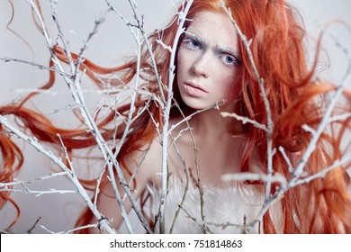 Redhead girl with long hair, a face covered with snow with frost. White eyebrows and eyelashes in frost, a tree branch covered with snow. Snow Queen and winter. Winter makeup woman face, red head