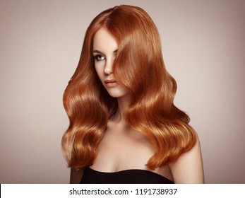 Redhead Girl with Long Healthy and Shiny Curly Hair. Care and Beauty. Beautiful Model Woman with Wavy Hairstyle. Make-Up and Black Dress