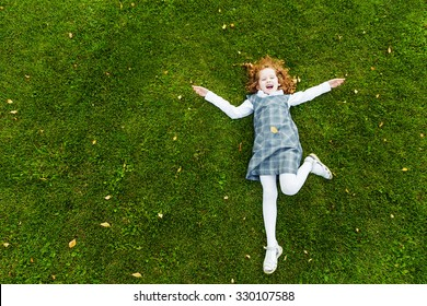 Redhead girl lying on the green grass in park, high top view, happy childhood, back to school, education concept.