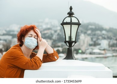 Redhead girl in a medical mask with a headache isotated on a rooftop, epidemic of a coronavirus. Depressed Woman with coronavirus symptoms.  SARS-CoV-2. COVID-19.