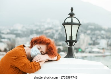 Redhead girl in a medical mask sleeping isotated on a rooftop, epidemic of a coronavirus. Depressed woman with coronavirus symptoms.  SARS-CoV-2. COVID-19.