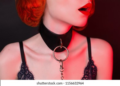 Redhead girl on black background. Sexual bdsm toy. Model with open mouth and red sensual lips. Lady with bondage on neck. Attire for playing bdsm games. Photo in low key lighting. Bondage with chain