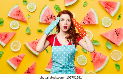 Redhead girl with oven gloves and apron on watermelon background
