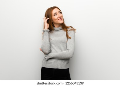 Redhead girl over white wall thinking an idea while scratching head