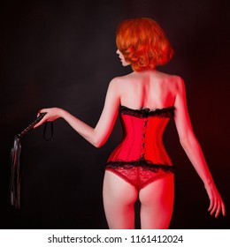 Redhead girl in red corset and whip on black background. Sexual bdsm fetish lingerie. Lady in laced corset. Outfit for bdsm games with seductive underwear and leather whip. Slim waist.
