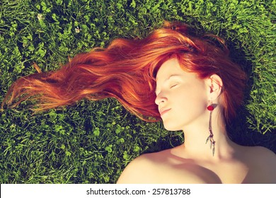 redhead girl relaxing lying on the grass. woman relaxation outdoor. photo with artistic effect. vintage toning. film retro style