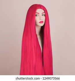 Redhead girl with shiny hair. Crimson coloring in salon. Long pink wig. Portrait of girl with perfect skin. Strong pink shiny hair without dandruff. Woman cosmetics. Crimson wig. Awesome wig