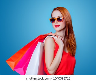 Redhead girl with shopping bags on blue background