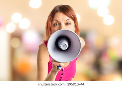 Redhead girl shouting with a megaphone on unfocused background