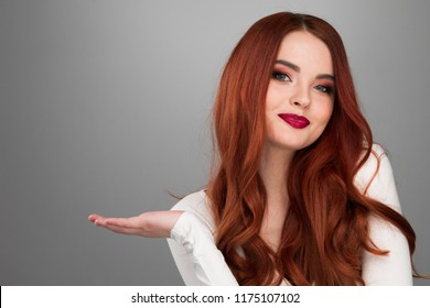 Redhead girl showing copy space on her palm, looking at camera, standing over gray background