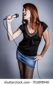 Redhead girl singing karaoke with microphone