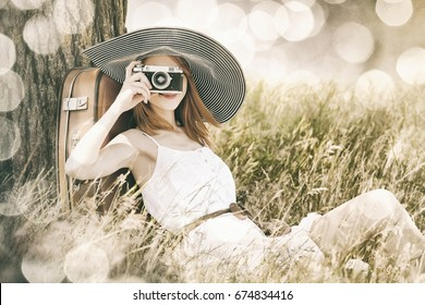 Redhead girl sitting near tree with vintage camera. Photo in old image color style