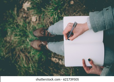 Redhead girl sitting on green spring grass writing down her thoughts in notebook. Pale hands and blank paper of notebook. Concept (idea) of thinking, dreaming, motivation, planning, studying.
