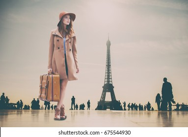 Redhead girl with suitcase and Eiffel tower on background