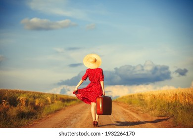Redhead girl with suitcase at outdoor.