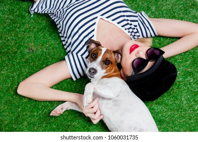 Redhead girl in sunglasses and hat with dog lying down on green spring time grass.