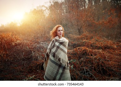 redhead girl at sunrise wrapped in a red blanket. Autumn season. Comfort concept. She is like a sun in autumn.