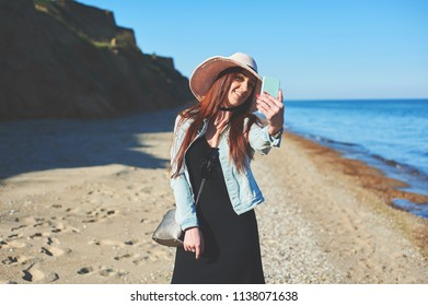 Redhead girl take a selfie. Wearing black dress and jeans jacket. Straw hat. Holding smartphone. Woman standing on sand. Retro toned image.