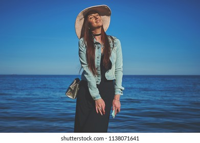 Redhead girl wearing black dress and jeans jacket. Straw hat. Holding smartphone. Woman standing on sand. Retro toned image.