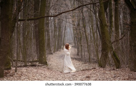 Redhead girl in white vintage dress walking in the spring forest.