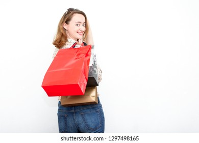 Redhead happy woman after shopping holding her bags and standing against light background.