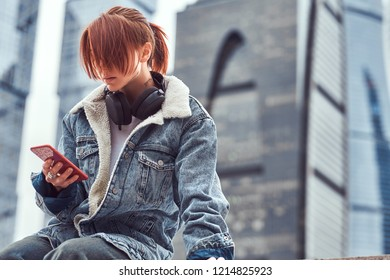 A redhead hipster girl with tattoo on her face using a smartphone sitting in front of skyscrapers in Moskow city at cloudy morning.