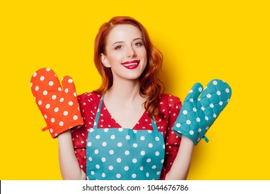 Redhead housewife with gloves and apron on yellow background