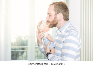 Redhead Man with Beard Kissing a Doll On Its Forehead