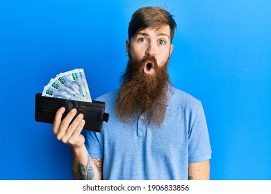 Redhead man with long beard holding wallet with south african rand banknotes scared and amazed with open mouth for surprise, disbelief face