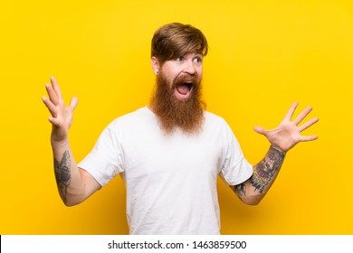 Redhead man with long beard over isolated yellow background with surprise facial expression