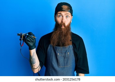Redhead man with long beard tattoo artist wearing professional uniform and gloves making fish face with lips, crazy and comical gesture. funny expression.