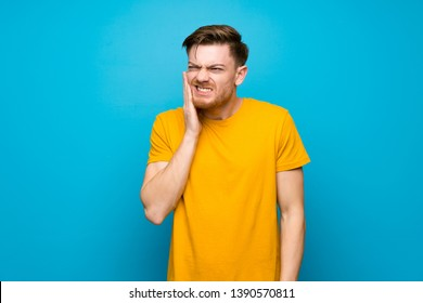 Redhead man over blue wall with toothache