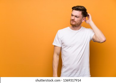 Redhead man over brown wall having doubts while scratching head
