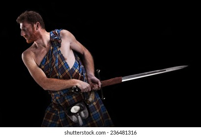 Redhead men in traditional scottish kilt and claymore sword