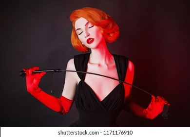 Redhead mistress dominant girl with stack on black background. Sexual bdsm toy. Woman submission. Outfit for playing bdsm games. Lady with leather stack in hand. Sensual dominant mistress