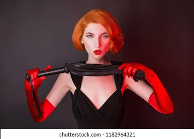 Redhead mistress dominant girl with whip on black background. Provocative bdsm toy. Woman submission. Outfit for playing bdsm games. Lady with leather whip in hand. Provocative dominant mistress