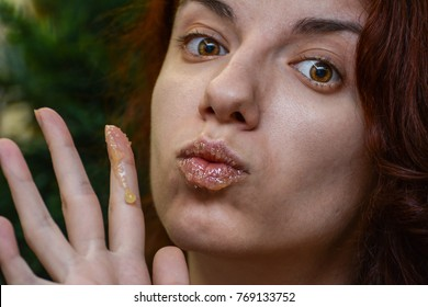 Redhead model using a homemade lip scrub made out of honey, sugar and olive oil
