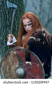 Redhead northern warrior woman with ax and shield getting ready to attack. Celtic woman into the woods