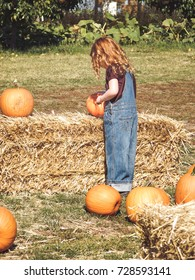Redhead in overalls looking at pumpkins during fall harvest