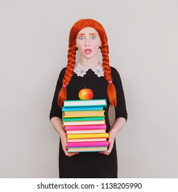 Redhead schoolgirl holds colored textbooks in hands on a gray background. Surprised girl in uniform is going to school. A red apple lies on the book. Young teacher. Back to school. Surprised face