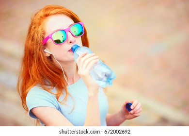 Redhead skinny girl in sunglasses drinking water