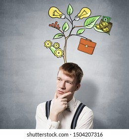Redhead student looks pensive and thinking about some problem. Puzzled boy with green plant drawing consisted of business infographic signs. Guy wears shirt and suspenders on background of grey wall