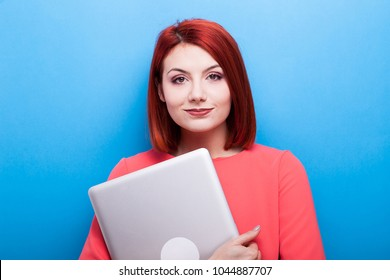 Redhead student woman with a laptop in hands on blue background
